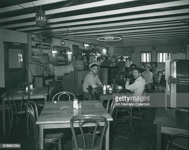 Black and white photograph featuring patrons sitting at tables and staff standing in background