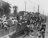 Black and white photograph of a large group of cotton hoers loading into open wagons at Memphis for the day's work in Arkansas June 1937 From the New...