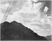 A black and white photograph of a mountain and transmission lines near the Hoover Dam towers for transmission lines can be seen on the peak of the...
