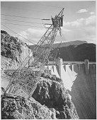 A black and white photograph of a transmission line tower and a portion of the Hoover Dam the tower was built on a cliff face and stands angled out...