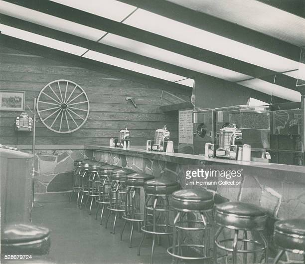 Black and white photograph of counter and stools in Chuck Wagon restaurant with wagon wheel on wall and juke box