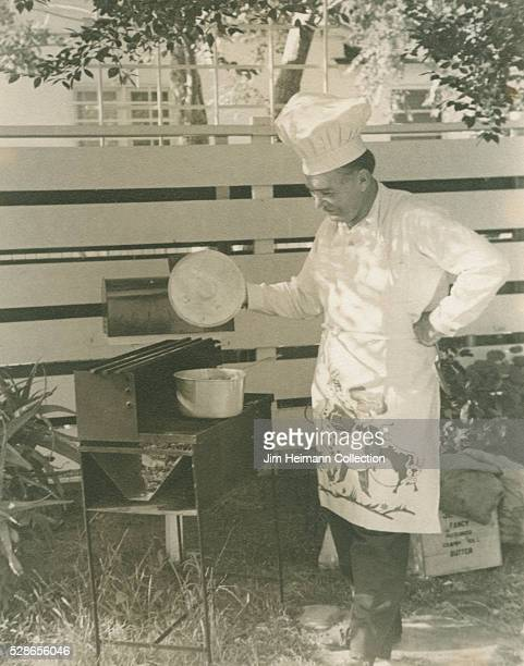 Black and white photograph of man wearing chef's hat and apron lifting up cover of pot on outdoor barbecue