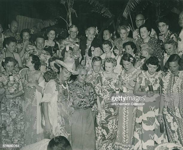 Black and white photograph of men and women wearing floral long dresses and leis outside at night Palm trees in background