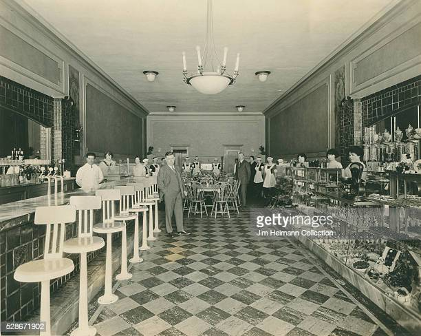 Black and white photograph of staff posing inside Elite Restaurant with glass display cabinet counter and checked floor