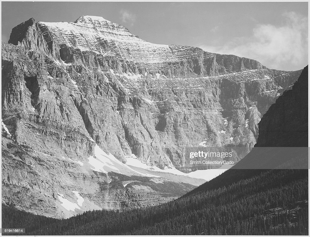 A black and white photograph of the side of a mountain in Glacier National Park the sunlit face of the mountain consists of bare rock that has bands...