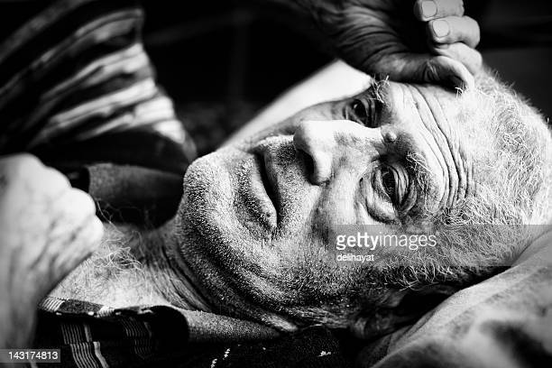 Black and white photograph or an elderly man laying down