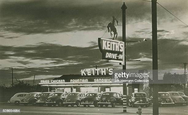 Black and white photographic postcard of Keith's DriveIn at night with cars parked in front