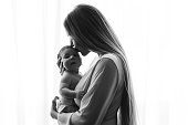 black and white picture of mother kissing little baby boy in front of curtains at home