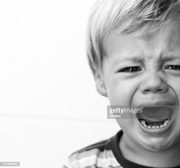 Black and white portrait of a crying young boy