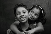 Black and white portrait of a Happy Boy and girl in a dark background