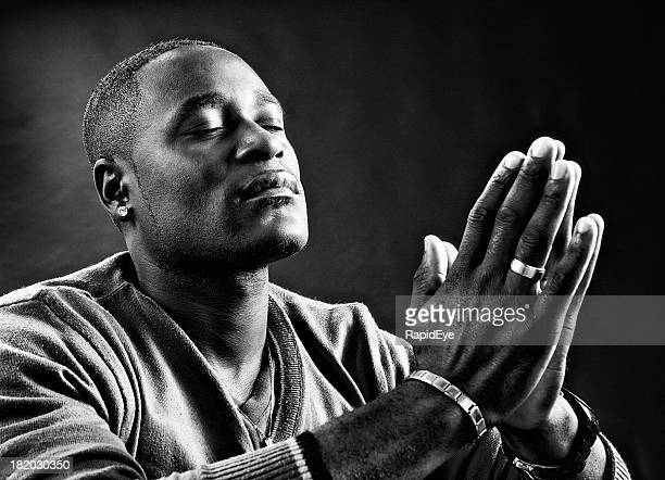 Black and white portrait of man praying devoutly