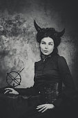 Black and white retro photo, woman demon. Girl with horns, effect of toning