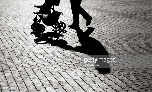 Black And White Shadow Of Baby Carriage On Sidewalk Stones