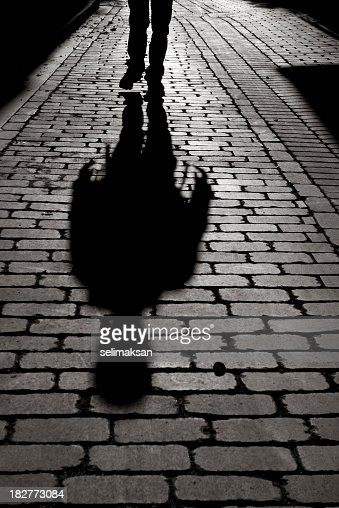 Black And White Shadow Of Man Walking On Sidewalk