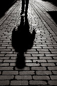 Black And White Shadow Of Man Walking On Sidewalk