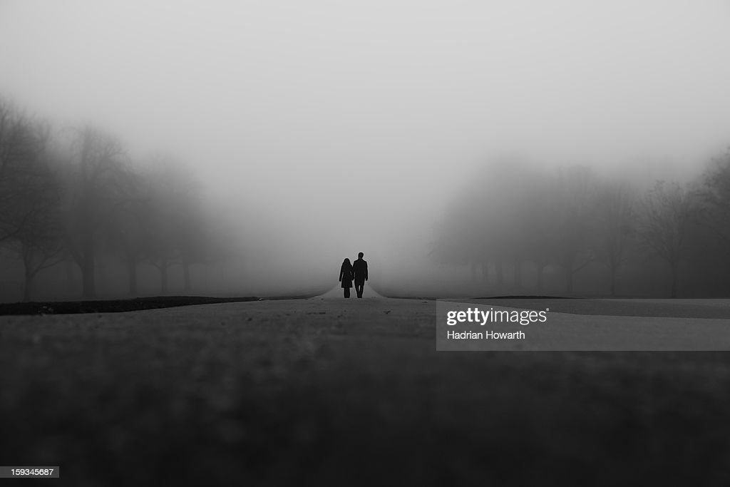 CONTENT] Black and white shot of couple waking together along Windsor's 'long walk' in thick fog with symmetry of misty trees.