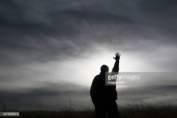 Black and White Silhouette Man With Hand Outstretched in Worship