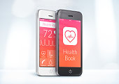 Black and white smartphones with health care book app on the screen are close to each other in half turn and rotated at a slight angle.