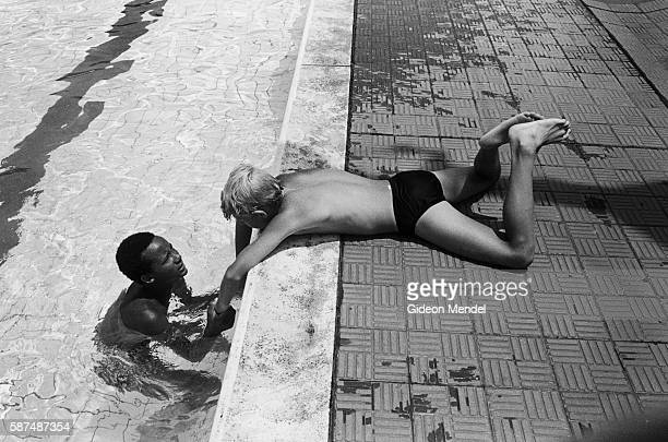Black and white South African schoolchildren relax at the Yeoville Park pool in Johannesburg's Yeoville neighborhood Under apartheid laws the pool is...