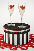 Black and white striped hatbox with glass of sparkling wine and strawberry, Studio shot against white background