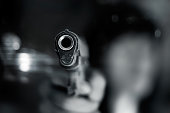 Black and white, woman pointing a old gun to front with one Hand on dark background