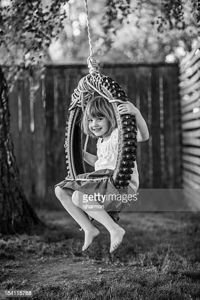 Schwarze und weiße junger Mädchen In Reifenschaukel einfachen Kleid