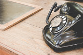 Black antique vintage analog telephone dialing or scrolling phone on old wall with old slate. Contact us concept.