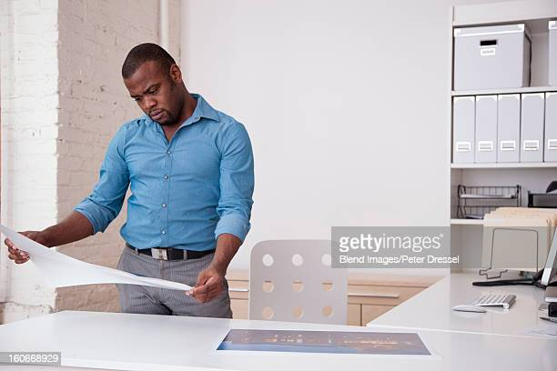 Black architect looking at blueprints in office