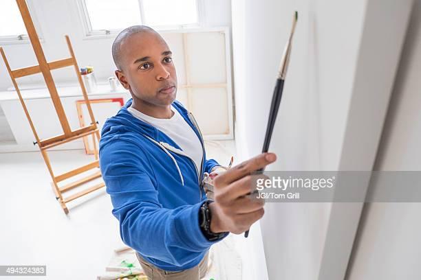 Black artist painting in studio