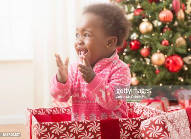 Black baby girl playing in Christmas gift box