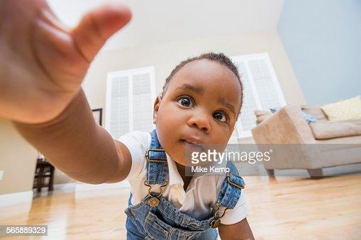 Black Baby Reaching For Camera On Living Room Floor Stock ...
