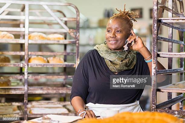 Black baker talking on cell phone in bakery kitchen