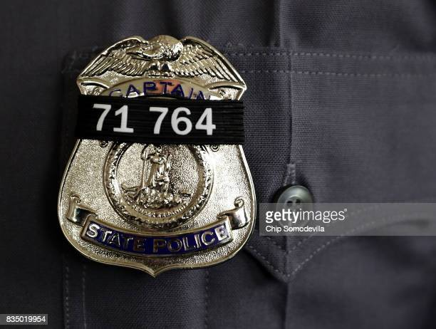 A black band with the badge number of Virginia State Police TrooperPilot Berke MM Bates is worn on the badges of fellow troopers during his funeral...