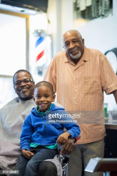 Black barber and customers smiling in retro barbershop