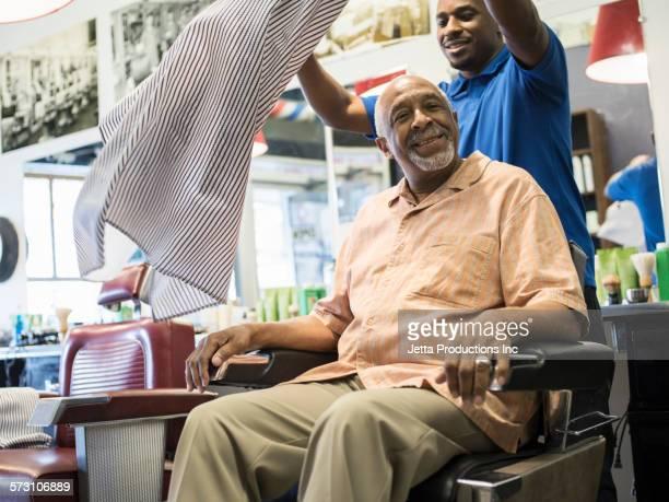 Black barber spreading apron over customer in retro barbershop