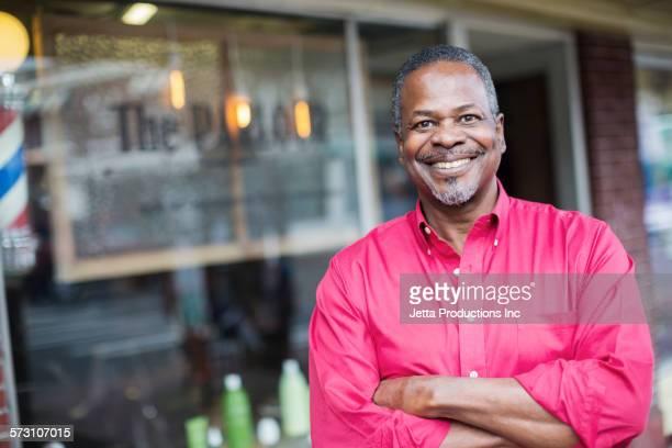 Black barber standing outside retro barbershop