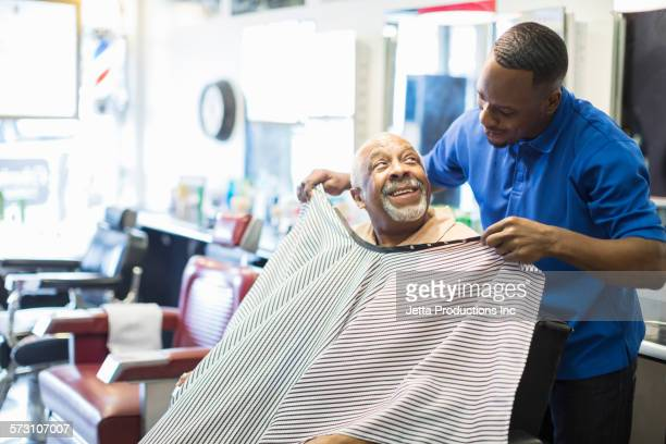 Black barber tying apron on customer in retro barbershop