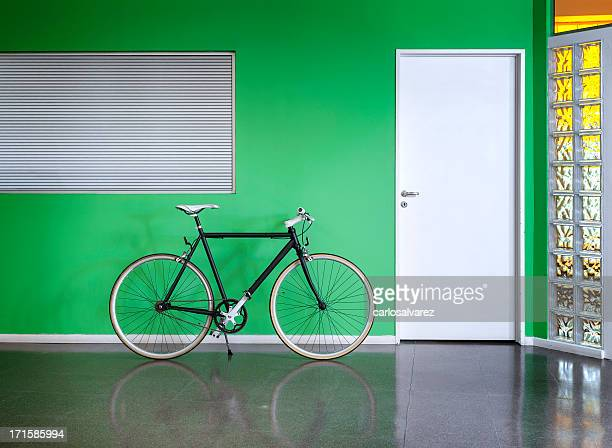 Black bicycle against a green wall
