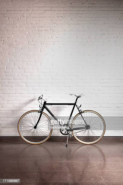 Black bicycle by a white brick wall