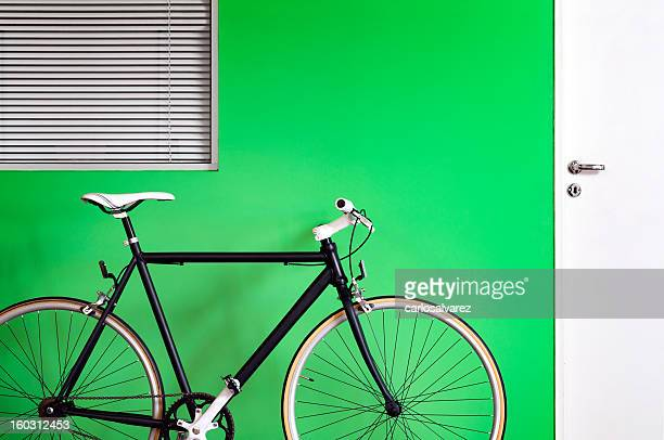 Black bicycle green wall