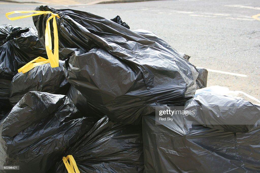 Black bin liners on street : Stock Photo