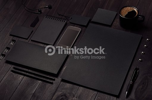 Black blank stationery set with phone, earphone, coffee on dark wood background, inclined. : Stock Photo