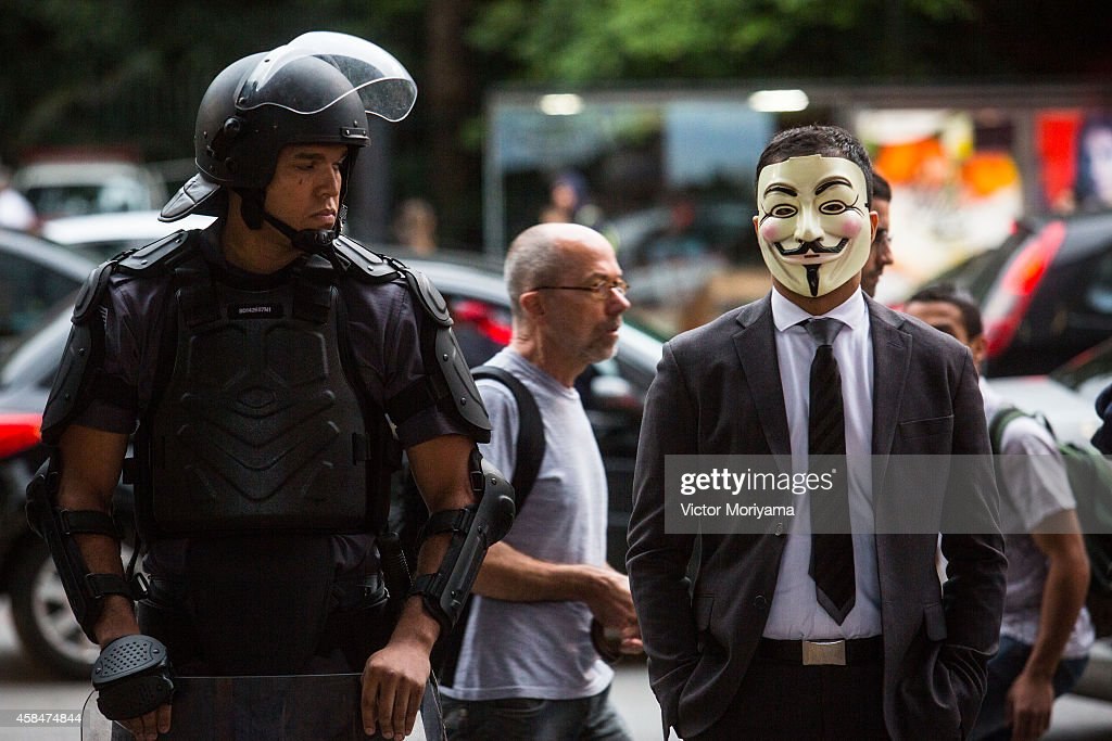 Black Bloc demonstrator stands next to a police officer during a protest against the lack of water that is affecting the entire state of Sao Paulo...