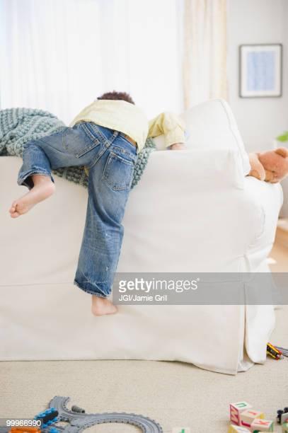 Black boy climbing over back of sofa