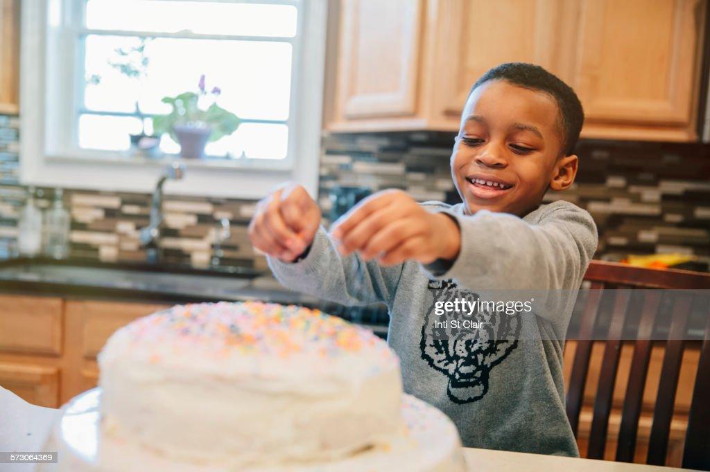 Black boy decorating cake in kitchen