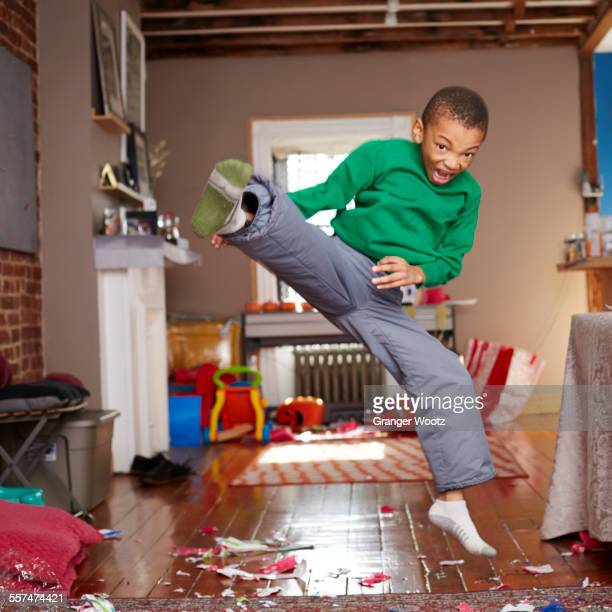 Black boy doing karate kick in living room
