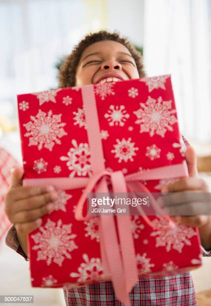 Black boy holding Christmas present