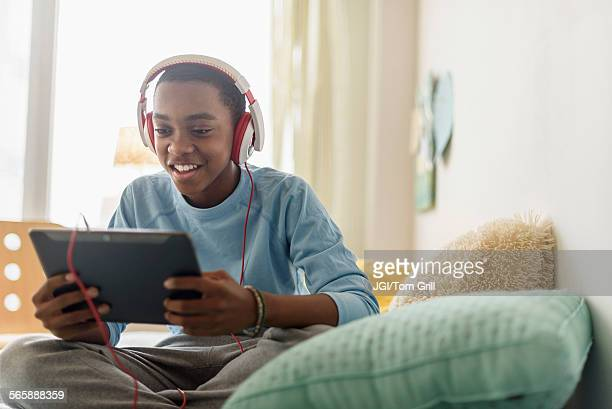 Black boy in headphones using digital tablet