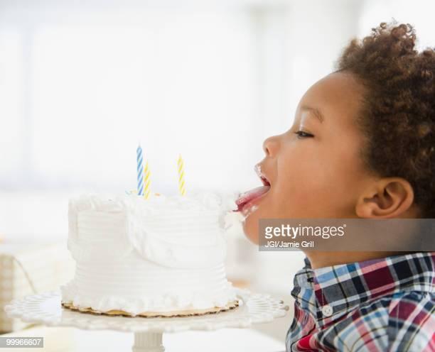 Black boy licking birthday cake