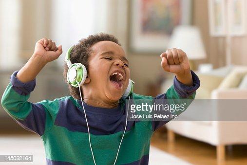 Black boy listening to music on headphones : Stock Photo
